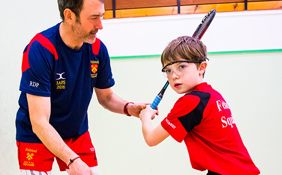 A Felsted squash trainer instructing a young pupil