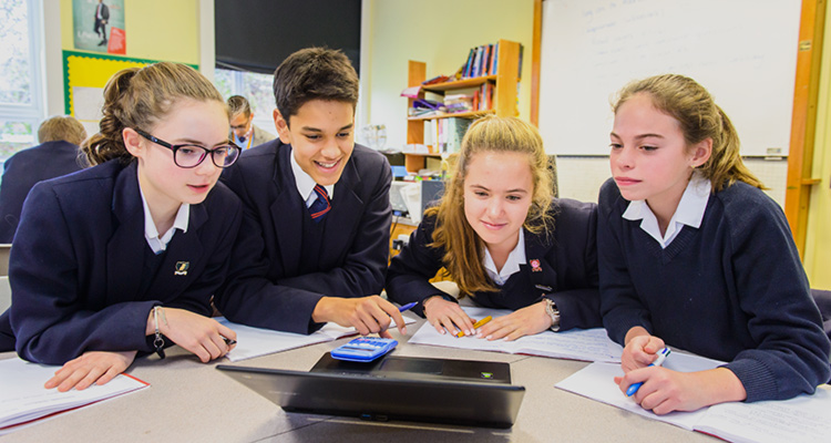 Four Felsted students sit around a laptop during class